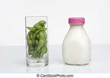 Soy and Milk - glass of soybeans next to glass jar of milk