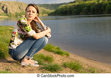 Attractive young woman sitting beside a lake - Attractive...