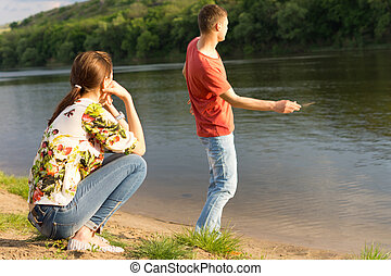 Young man skimming stones across water - Young man skimming...