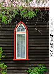 Single Vision - Pointed arch window in dark weatherboard...
