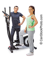 Young man and woman with elliptical cross trainer