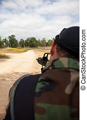 armed man with a gun is holding at gunpoint, the military...