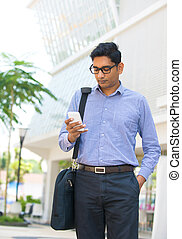 Young Indian Businessman using a smart phone standing...