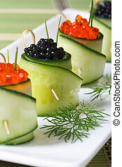 cucumber rolls with salmon red and black sturgeon caviar on...
