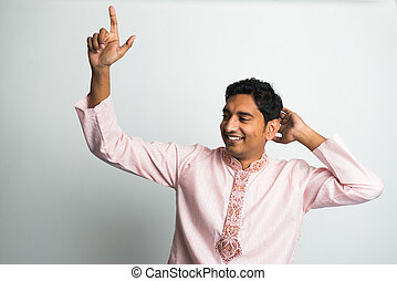 young indian male in traditional cloths dacing with bhangra...