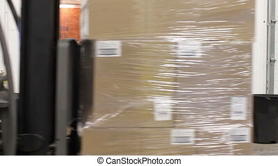 Forklift Loading Truck - A forklift moves palettes of boxes...