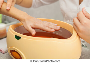 Spa salon. Manicure. Paraffin hand bath.