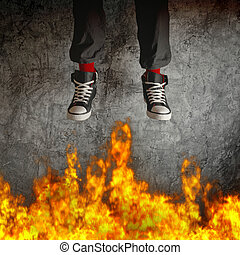 Young man in sneakers is jumping over fire flames Concept of...