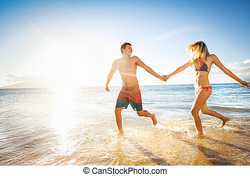 Happy couple running on a tropical beach in the ocean at...