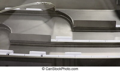 Industrial Conveyor System - Close-up of small plastic parts...