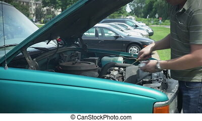Checking oil under hood of car vehicle. Adding oil.
