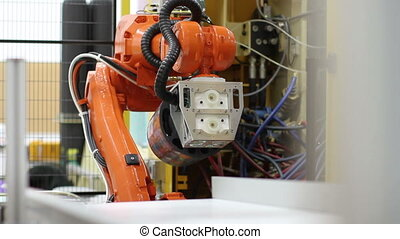 Industrial Robotic Arm - A robotic arm in a factory, as it...