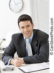 Businessman working at desk - Happy young businessman...