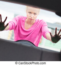 Woman pushing a car.