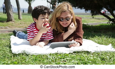 mother and son using digital tablet in park