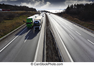 trucks driving on freeway at sunset - two trucks overtaking...