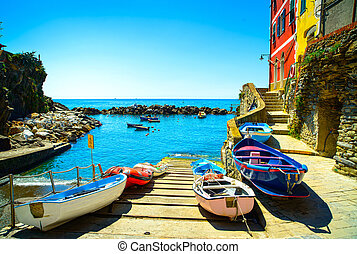 Riomaggiore village street, boats and sea in Five lands,...