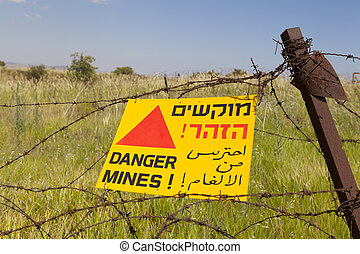 Mines - Minefield sign on a barbed wire fence in hebrew...