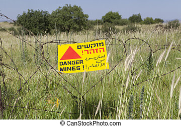 Danger Mines - Minefield sign on a barbed wire fence in...