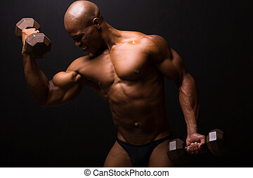 african male bodybuilder exercising on black background