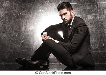 serious young elegant man sitting and looking at the camera
