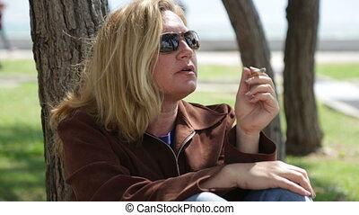 Sad woman smoking in park
