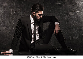 pensive young business man resting on the floor in studio