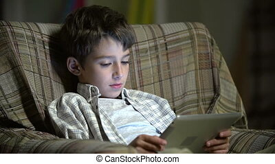 Childhood Online - Static close up of boy sitting in...