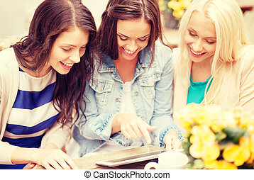 three beautiful girls looking at tablet pc in cafe -...