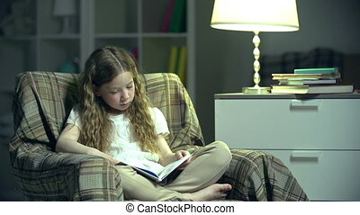 Little Bookworm - Handheld shot of girl in nursery reading a...