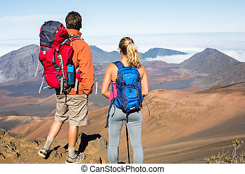 Man and woman hiking on beautiful mountain trail. Trekking...