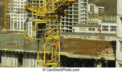 High tower crane swings round on building construction site...