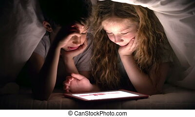 Staying up Late - Siblings examining pics on tab under...