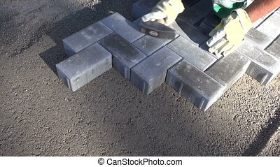 worker fixing new pavement brick