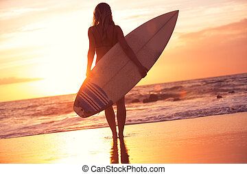 Silhouette surfer girl on the beach at sunset - Silhouette...