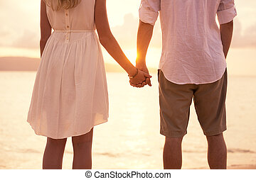 Couple on the beach sunset - Romantic couple in love holding...