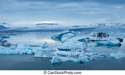 blue icebergs floating under midnight sun - Panning right to...