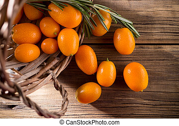 Kumquat. - Kumquat berries on wooden background. Citrus...