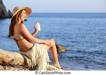 Woman on holidays on the beach applying sunscreen protection...