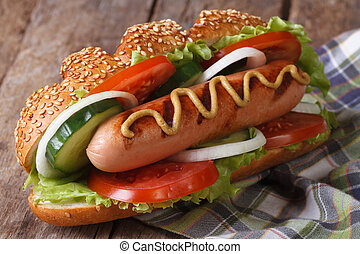 Hot dog with sausage, mustard and vegetables close up on an...