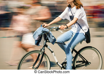 Cyclist in traffic on the city roadway - Hot day in the...