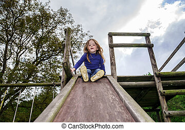 Young girl and wooden teeter board. Personal playground.
