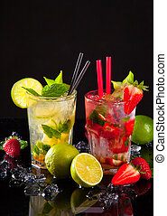 Summer drinks, lime and strawberry on black stone,table.