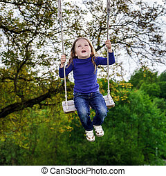Cute little girl swinging on seesaw to the sky