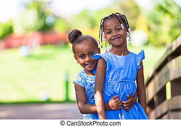 Outdoor portrait of a cute young black sisters smiling -...