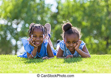 Outdoor portrait of a cute young black sisters lying down on...
