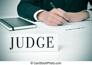 judge - a man wearing in his desk with a nameplate in front...
