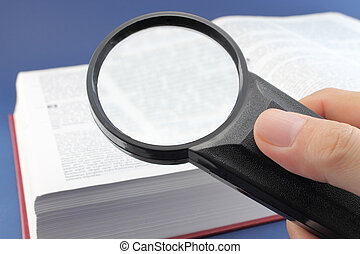 Reading a book with magnifying glass - Hand with a...