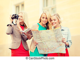 women with tourist map and camera in the city - holidays and...