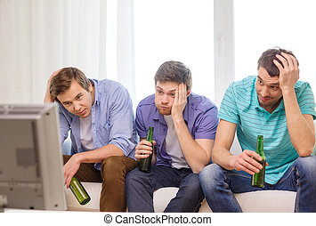 sad male friends with beer watching sports